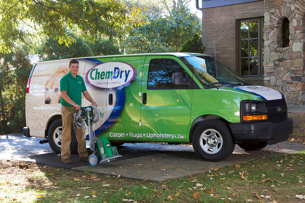 chem-dry technician with carpet cleaning powerhead by van