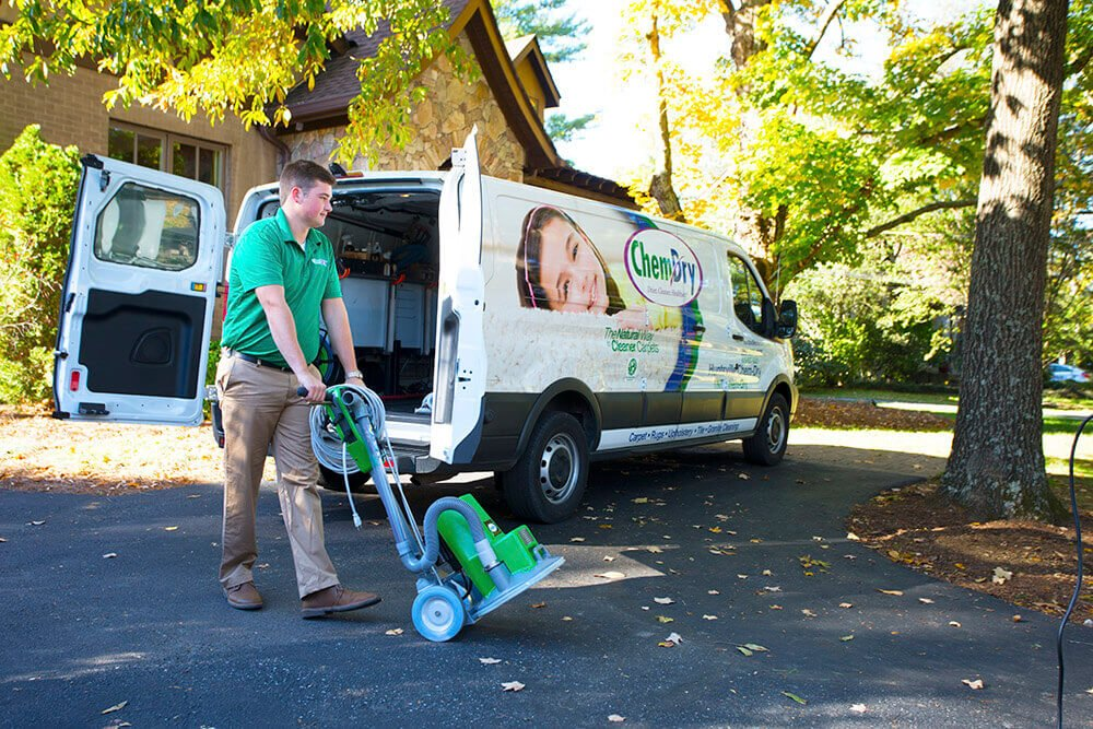 chem-dry carpet cleaning tech moving powerhead out of van outside of home